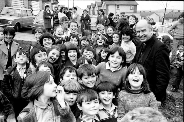April 1980... Bishop of Derry, Dr Edward Daly, pictured with a group of kids during a pastoral visit to the Top of the Hill in the Waterside.