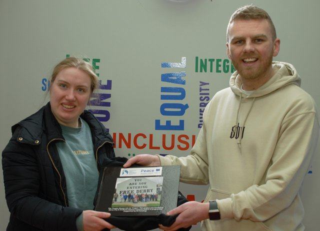 Gavin Melly and Participant Meabh Fisher presenting 32 photo book and hoodie for completing the project