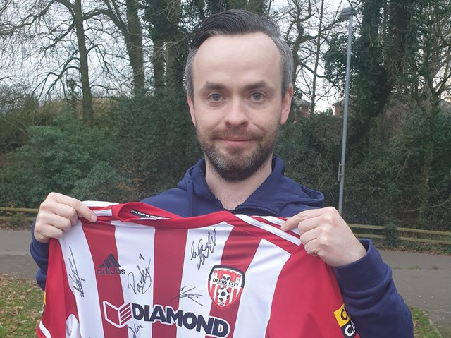 Supporter Colin O'Kane receives a signed Derry City jersey for a raffle he had organised.