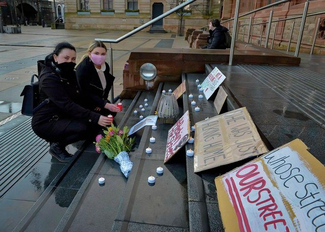 Sisters Andrea and Micaela McGillian place lighted candles on the Guildhall steps recently in remembrance of Sarah Everard. DER2110GS – 109