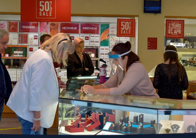A shop assistant in a city centre jewellers wearing a face shield in early 2020. DER2027GS - 020