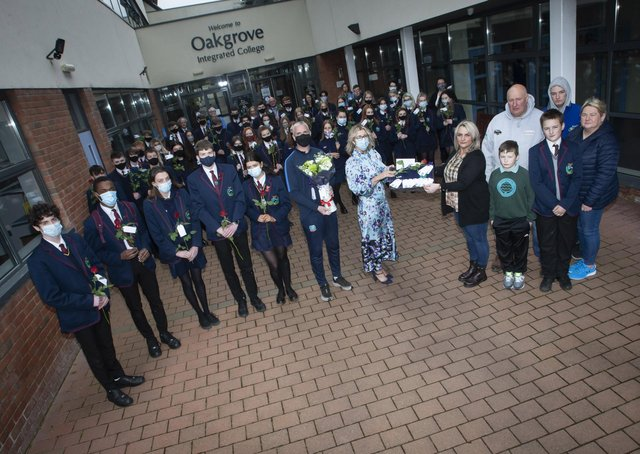 Mrs Katrina Crilly (Principal) presenting Leeâ€TMs mum Jacqueline Gurney with Lee's Oakgrove Leavers Hoodie at Oakgrove Integrated College on Monday. Included are sixth form students and members of staff. On right also are Lee's dad Derek, brothers Jay and Cain, and family friend Melanie Toland. (Photos: Jim McCafferty Photography)