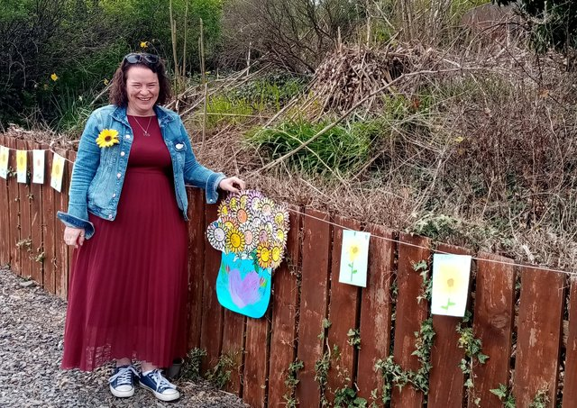 Geraldine Mullan pictured with sunflowers made by Gaelscoil Riabhach, Co. Galway