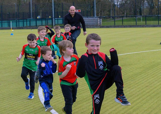Paul Simpson, Doire Trasna coach, and nursery footballers getting some stretching exercise during a training session at the Foyle Arena recently. Photos: George Sweeney. DER2115GS – 068