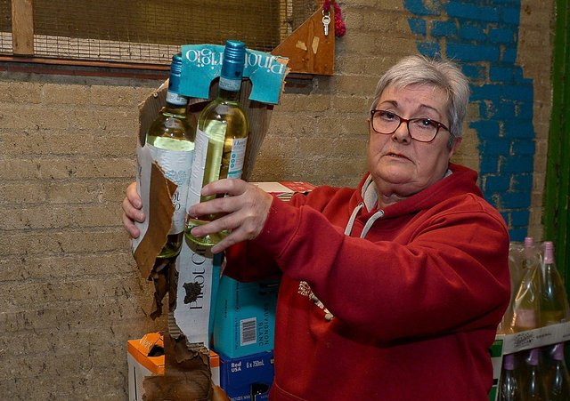 Proprietor Ruby Butler inspects the water damage to stock in the storeroom of O'Kane's Liquor Store in Shantallow. DER2118GS – 006