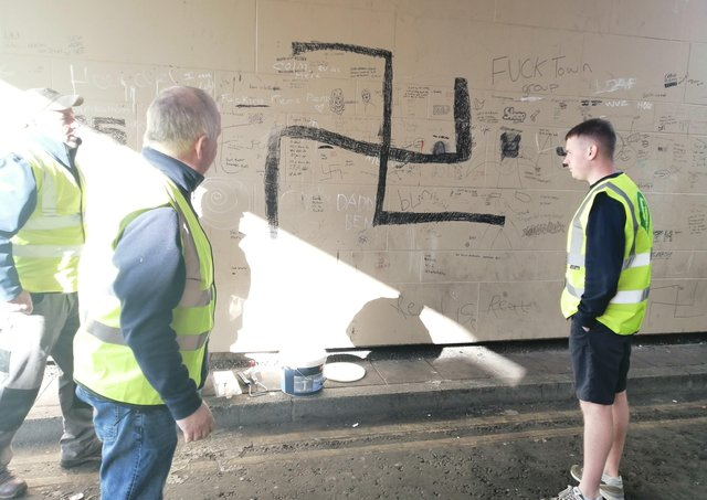 Members of the Martin McGuinness Cumann get ready to paint out the offensive graffiti.