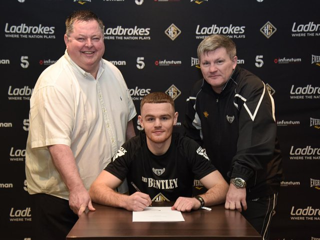 Brett McGinty signs his contract with Hennessy Sports overseen by Mick Hennessy and trainer Ricky Hatton