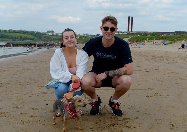 Eirn Hamilton, Caolan Kearney and Fudge the dog, from Derry, at Lady's Bay beach, Buncrana yesterday afternoon. Photos: George Sweeney. DER2122GS – 015