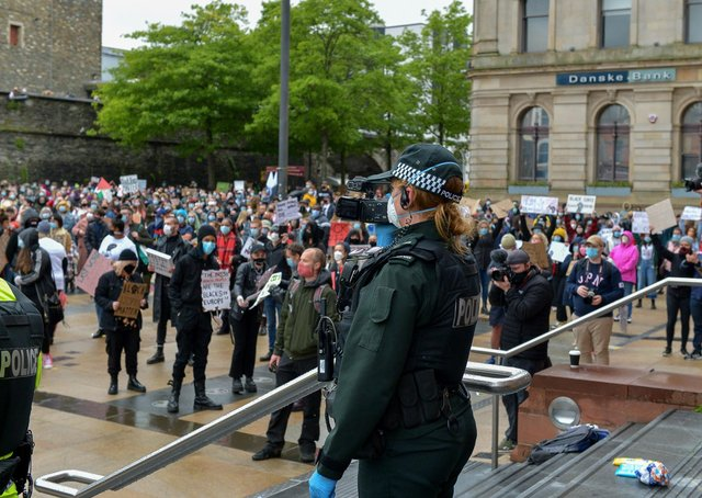 A female PSNI officer videos people attending the recent Justice for George Floyd rally held in Guildhall Square. DER2320GS – 039