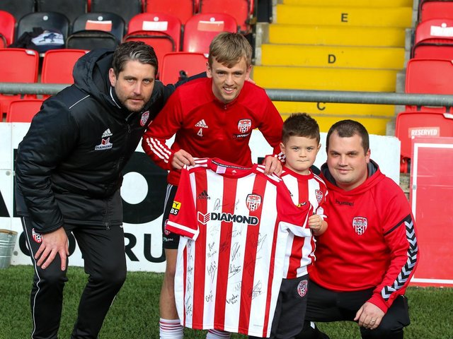 Derry City manager Ruaidhri Higgins and vice captain Ciaron Harkin present a signed Derry jersey to five year old Caleb Toland, who underwent major brain surgery last month, and his father Richie. Photographs by Kevin Moore