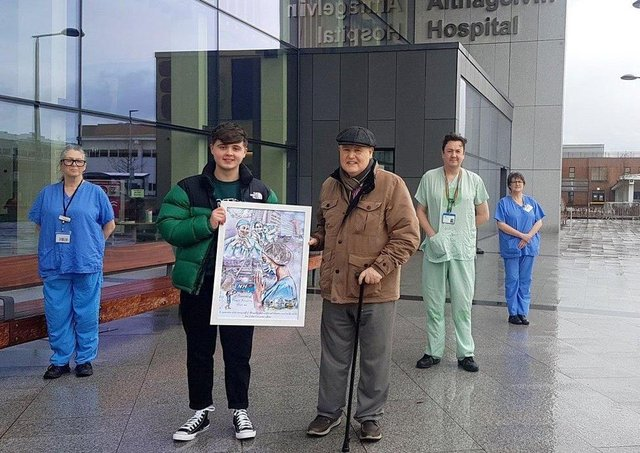 Ethan Deery and his grandfather Neil present pictures to staff at Altnagelvin Hospital.