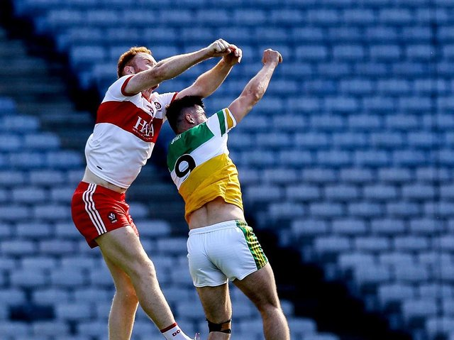 Conor Glass takes to the skies to break a high ball against Offaly's Eoin Carroll in Croke Park on Saturday. (Photo: Lorraine O'Sullivan/INPHO)