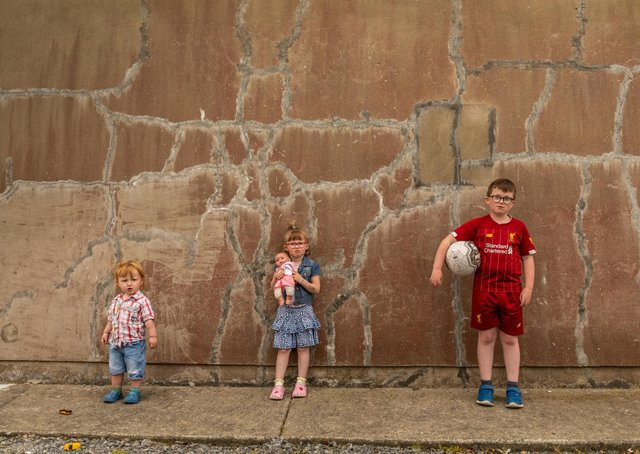Nine-year-old Tiernan Long from Inch Island with his younger siblings five-year-old Samarah and two-year-old Matthew outside their Mica damaged home. (Photo: Brendan Diver)
