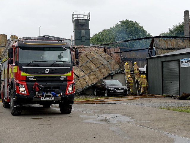 Firefighters at the scene of aftermath of the blaze on Railway Street, Strabane, that destroyed a coffin-making business on Sunday afternoon last. Photo: George Sweeney / Derry Journal.  DER2127GS – 005