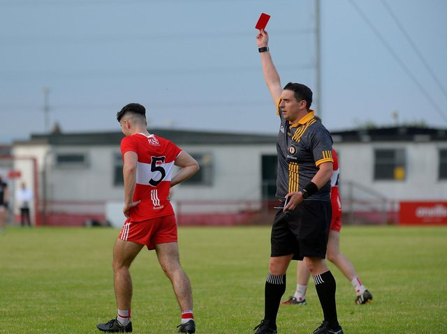 Derry's James McGurk receives a late red card from referee Kieran Eannetta after a foul on Monaghan keeper Ryan Farrelly. (Photo: George Sweeney)