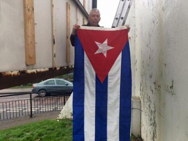 Sinn Féin activist Mickey Kinsella raising the Cuban flag at Free Derry Corner to mark the death of Fidel Castro in 2016.