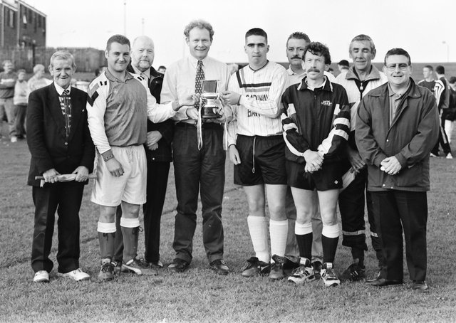 Martin McGuinness presenting the Bronco Bradley Memorial Cup to Gary Barnfield, captain, Ardnamoyle Celtic,                                                      who defeated Annie's Bar in the final held at Leafair pitches. Included, from left, are Pash Doherty, linesman, Bobby Sheerin, Conor McCallion, captain Annie's Bar, Martin McGilloway, organiser, Eamon Wilkinson, referee, Danny McCloskey, linesman, and Tony Hasson.