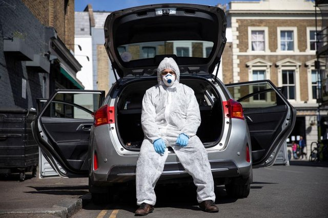 Uber driver Yasar Gorur wears personal protective equipment while cleaning his vehicle (Photo: Hollie Adams/Getty Images)